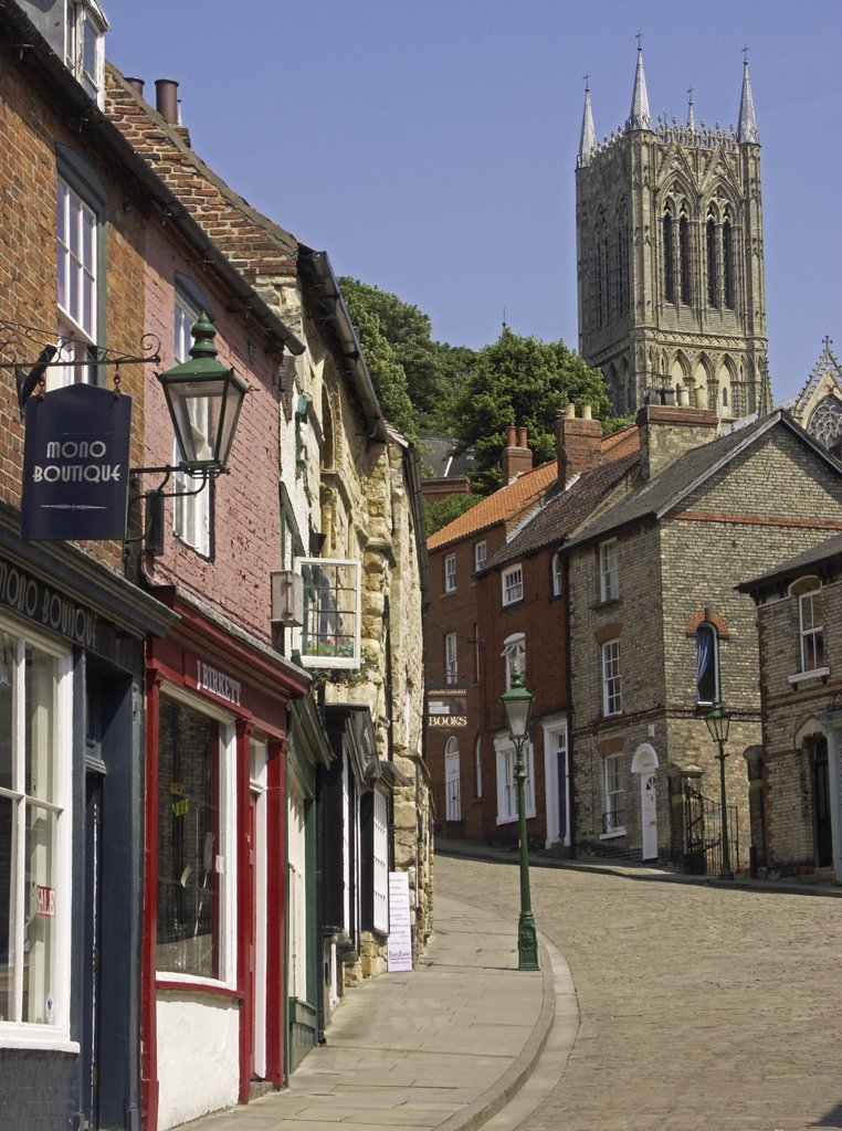England, Lincolnshire, Lincoln. Medieval buildings line the cobbled street and flagstoned pavement leading to the cathedral quarter at the top of Steep Hill in Lincoln. : Stock Photo