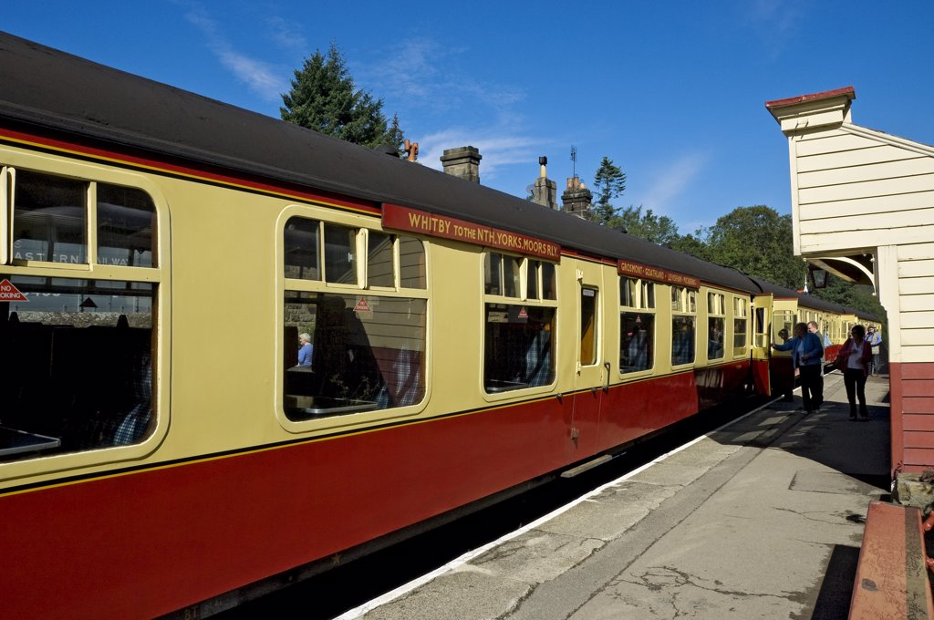 Stock Photo: 4282-30016 England, North Yorkshire, Goathland. Passengers boarding a train carriage at Goathland Station on the North Yorkshire Moors Railway.