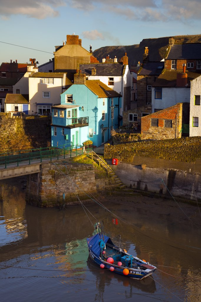 Stock Photo: 4282-30181 England, North Yorkshire, Staithes. A fishing boat in the sheltered harbour at Staithes at dusk.