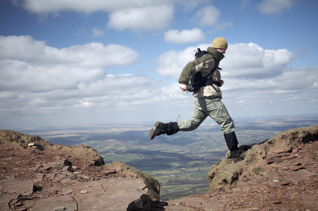 Stock Photo: 4282-30322 Wales, Powys, Pen y Fan. A walker leaping over a gap in a path on Pen Y Fan, the highest peak in South Wales.