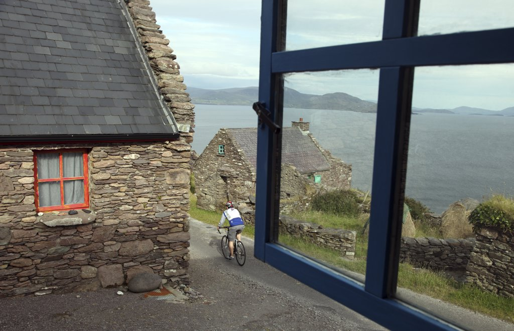 Republic of Ireland, County Kerry, Ballinskelligs. Cyclist in Cill Rialaig, an 18th century deserted village destined for demolition until rescued by arts patron Noelle Campbell Sharpe and restored as an artists retreat where artists may stay free of charge. : Stock Photo