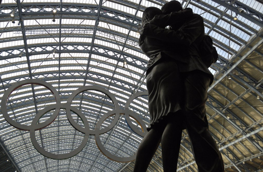 England, London, King's Cross. The Lovers statue, a 20-tonne bronze sculpture by Paul Day and a giant set of Olympic rings in St Pancras International. : Stock Photo