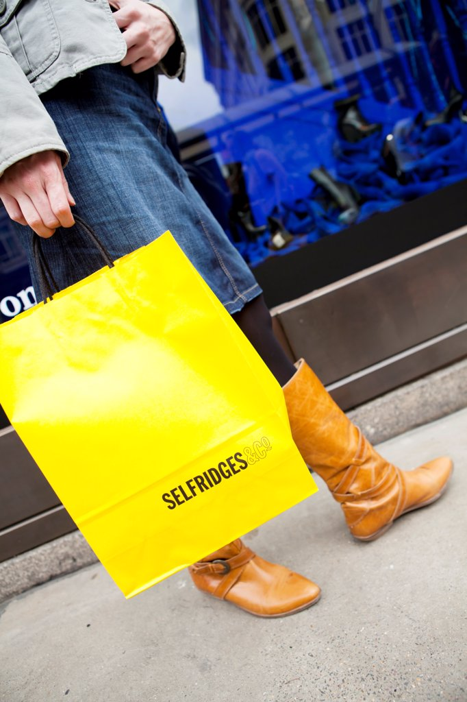 England, London, Oxford Street. A young lady on Oxford Street with bright yellow shopping bags from Selfridges. : Stock Photo