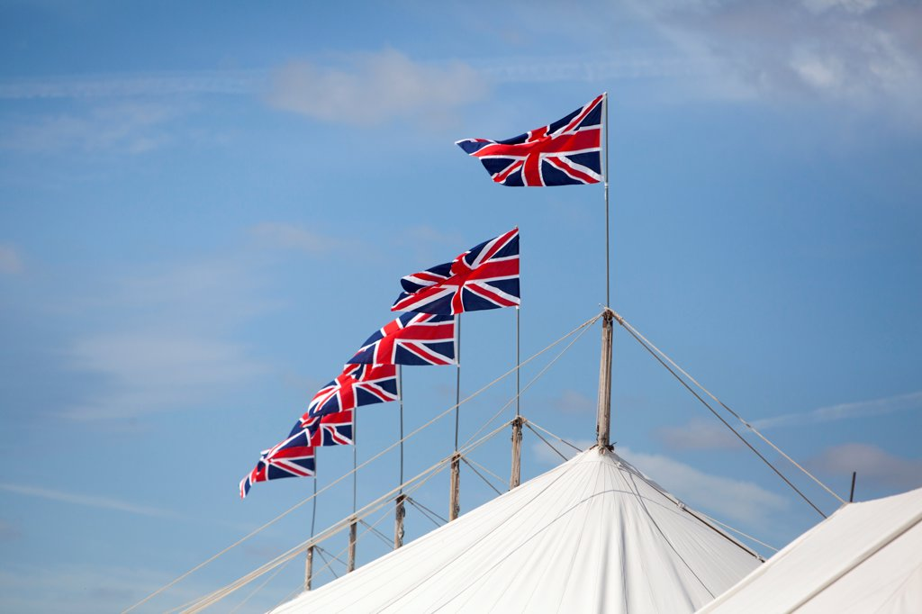 Stock Photo: 4282-30992 England, West Sussex, Goodwood. A series of Union Jack flags on top of a marquee at Goodwood revival.