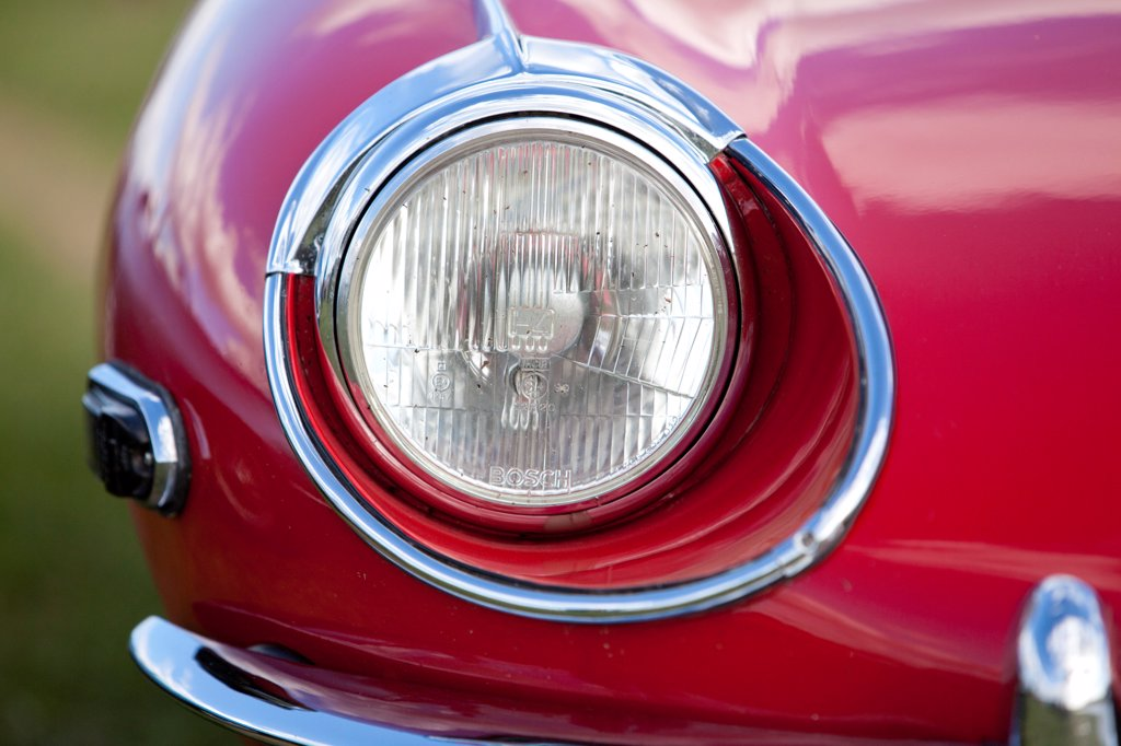 England, West Sussex, Goodwood. A close up view of the headlight of a Jaguar E Type classic car at Goodwood revival. : Stock Photo