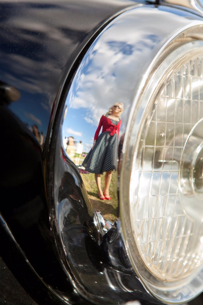 Stock Photo: 4282-31000 England, West Sussex, Goodwood. A girl in a black and white polka dot dress reflected in the chrome rim of a classic car's headlight at Goodwood Revival.