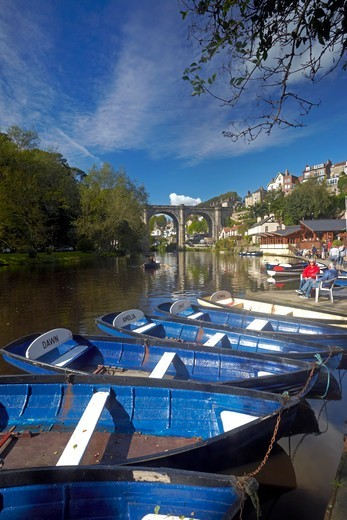 Stock Photo: 4282-31333 England, North Yorkshire, Knaresborough. Rowing boats on the River Nidd at Knaresborough with the Victorian railway viaduct in the background.