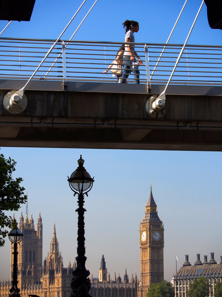 Stock Photo: 4282-31636 England, London, Golden Jubilee Footbridge. People walking across Golden Jubilee footbridge with the Houses of Parliament in the background.