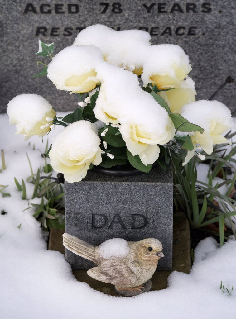 England, Oxfordshire, Radley. Snow-covered memorial in Radley village church graveyard. : Stock Photo