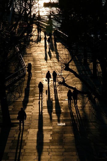 Stock Photo: 4282-32676 England, London, South Bank. Shadows and silhouettes of pedestrians walking along the Queen's Walk alongside the River Thames at South Bank.