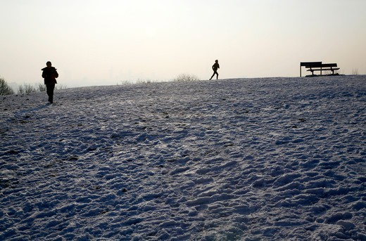 England, London, Hampstead Heath. Walker and jogger taking in the view from the top of a snowy Parliament Hill on Hampstead Heath. : Stock Photo