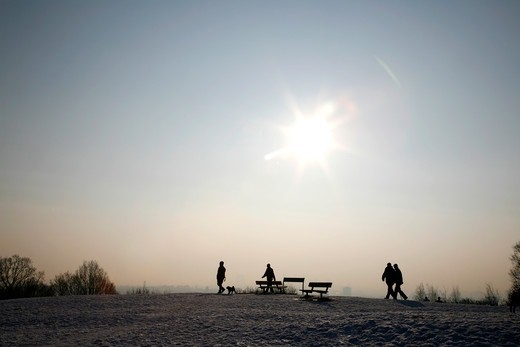 Stock Photo: 4282-32708 England, London, Hampstead Heath. Walkers taking in the view from the top of a snowy Parliament Hill on Hampstead Heath.