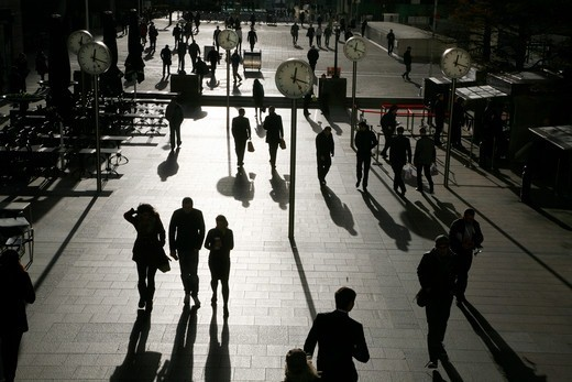 England, London, Canary Wharf. Shadows and silhouettes of pedestrians walking through Reuters Plaza at Canary Wharf. : Stock Photo