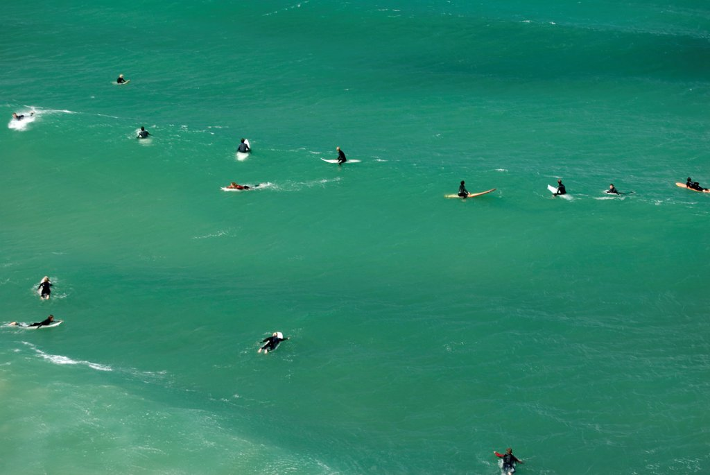 England, Cornwall, Newquay. Surfers in the water at Newquay. : Stock Photo