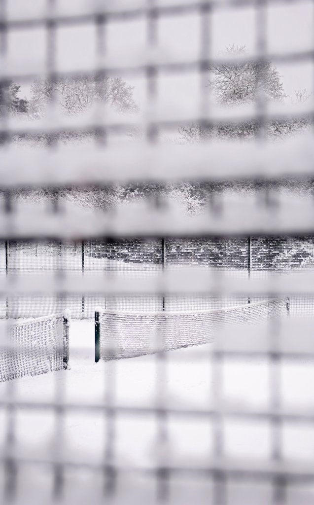 England, London, Camden. Looking through a snow-covered mesh fence at a snowed down tennis court in Waterlow Park in North London. : Stock Photo
