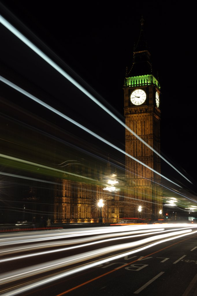 Stock Photo: 4282-3359 England, London, Westminster. Light trails from traffic crossing Westminster bridge by Big Ben and the House of Commons at night.