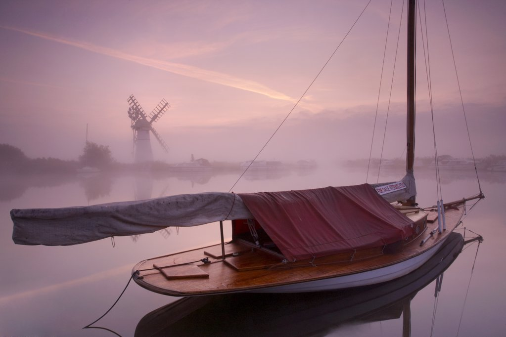 Stock Photo: 4282-3932 England, Norfolk, Thurne. A misty view across the water to Thurne Mill at sunrise.