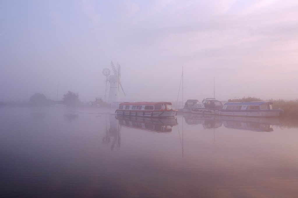 England, Norfolk, Thurne. A misty view across the water to Thurne Mill at sunrise. : Stock Photo