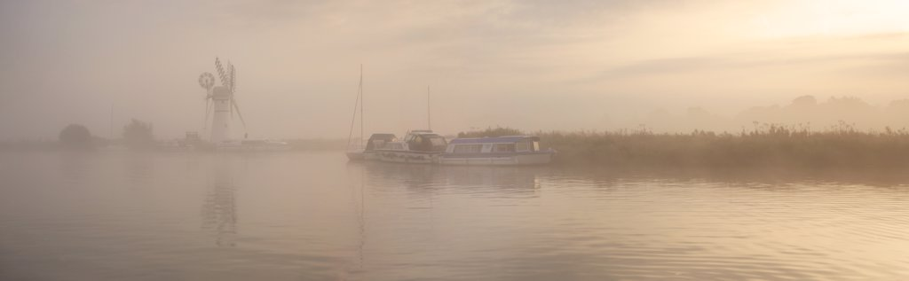 Stock Photo: 4282-4003 England, Norfolk, Thurne. A misty view across the water to Thurne Mill at sunrise.