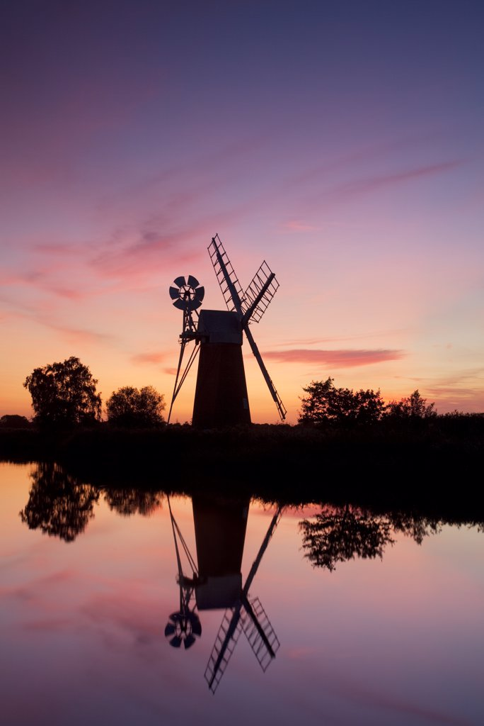 England, Norfolk, Near How Hill. Turf Fen drainage mill at sunset on the River Ant in the Norfolk Broads. : Stock Photo