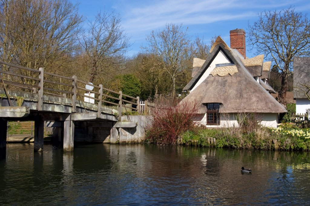England, Suffolk, Flatford. A wooden bridge over the River Stour leading to the 16th century Bridge Cottage, home to an exhibition on the artist, John Constable. : Stock Photo