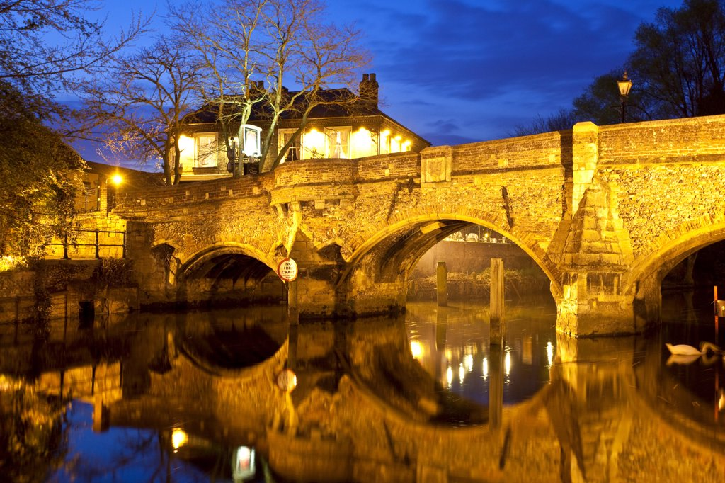 England, Norfolk, Norwich. The medieval Bishop Bridge over the River Wensum at night. The bridge was built in 1340 and is one of the oldest bridges still in use in England. : Stock Photo