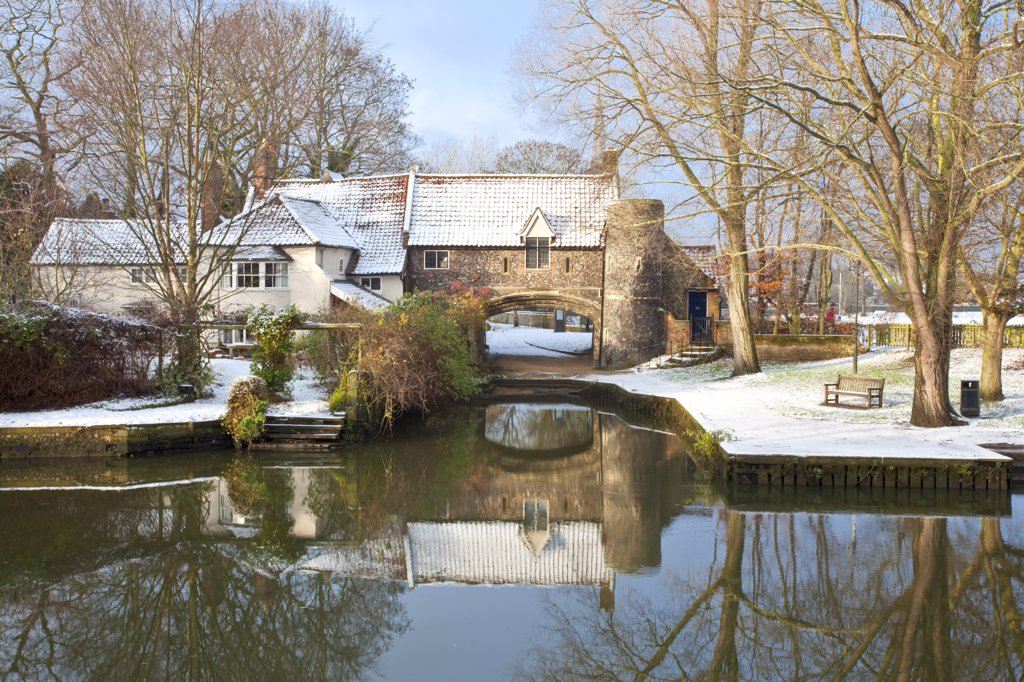 Stock Photo: 4282-4343 England, Norfolk, Norwich. Pulls Ferry, once a 15th Century watergate, on the River Wensum following winter snowfall. A canal used to run under the arch along which stone to build Norwich Cathedral was ferried.