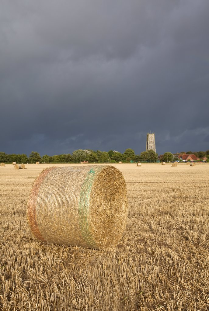 Stock Photo: 4282-4463 England, Norfolk, Winterton-on-Sea. View over bales of hay towards stormy clouds over Holy Trinity and All Saints Church at Winterton-on-Sea.