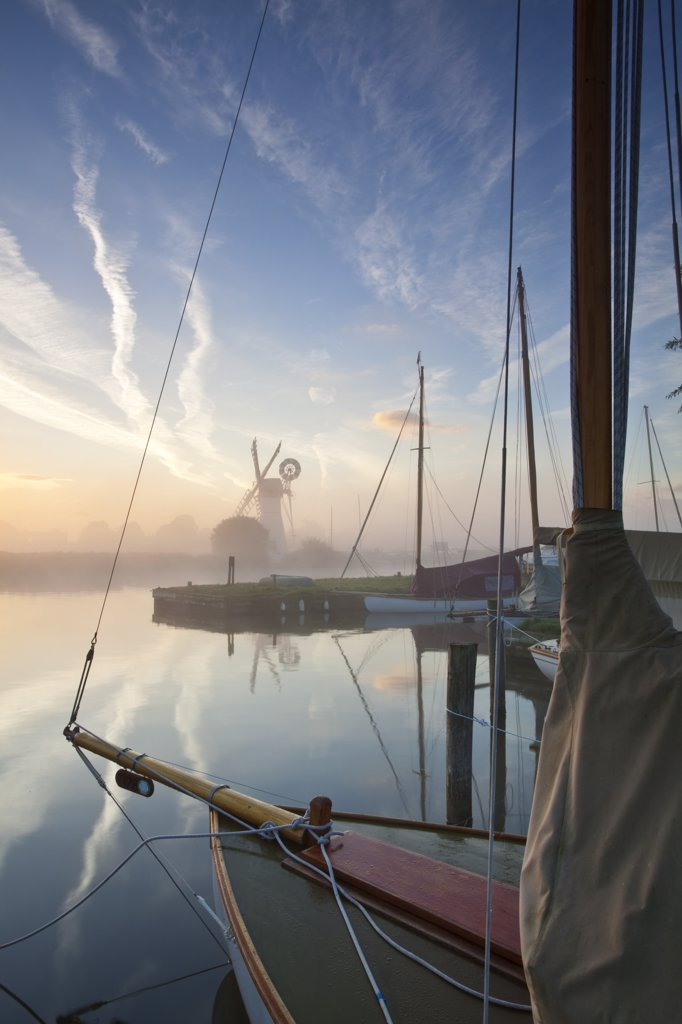 Stock Photo: 4282-4469 England, Norfolk, Norfolk Broads. View over the bow of a sailing boat on the River Thurne through dawn mist towards Thurne drainage mill on the Norfolk Broads.