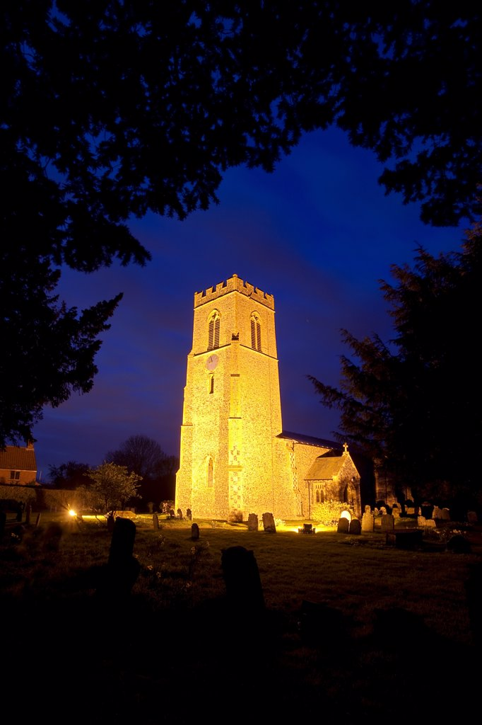 England, Norfolk, Mulbarton. St Mary Magdalen church, parts of which date back to the late 14th century, illuminated at night. : Stock Photo