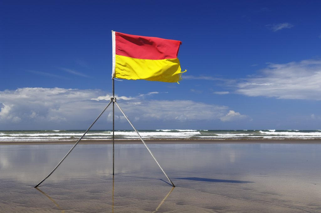 England, Devon, Westward Ho!. A lifeguard's safety flag on Westward Ho! beach. At Westward Ho! there are two miles of sandy beach known as the Golden Bay. : Stock Photo