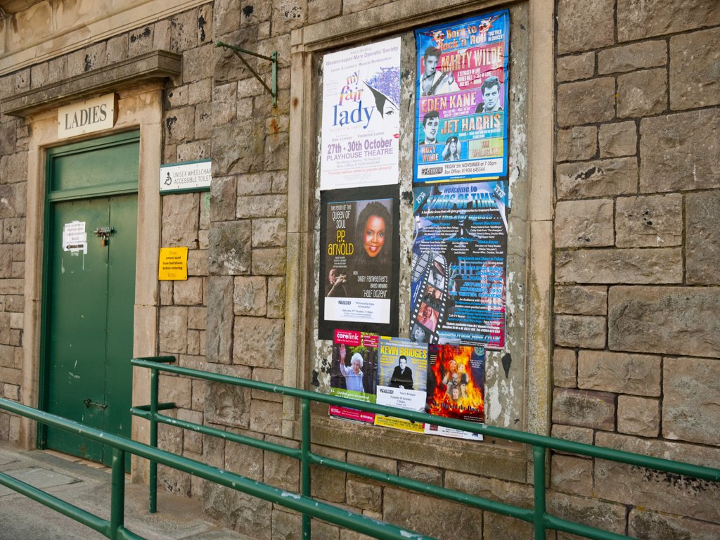 England, Somerset, Weston-super-Mare. Fly posters on the side of public toilets closed at the end of the holiday season in the seaside resort of Weston-super-Mare. : Stock Photo