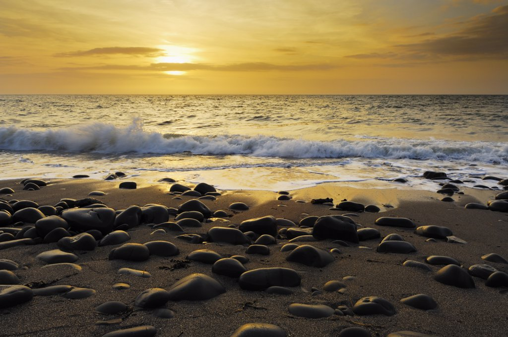 England, Devon, Westward Ho!. Waves washing onto the pebbled beach during sunset at Westward Ho! on the North Devon coast. : Stock Photo