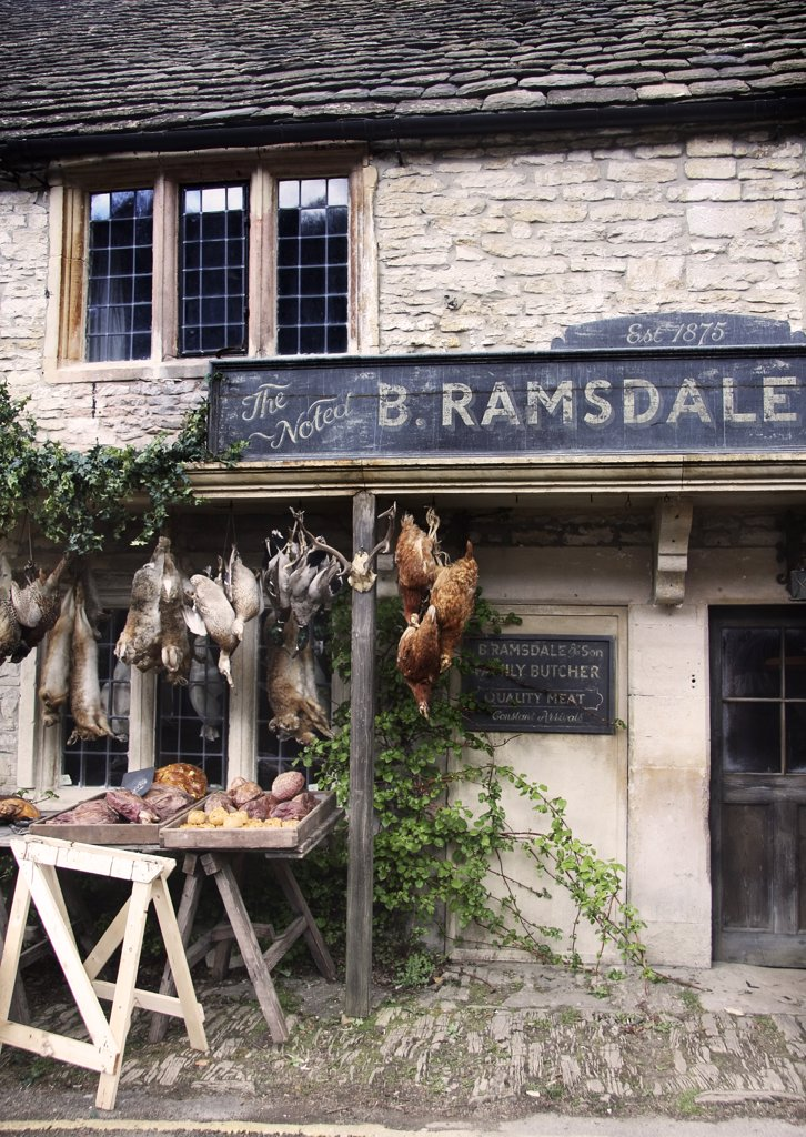 England, Wiltshire, Castle Combe. A view towards the front of a butcher shop in Castle Combe. : Stock Photo