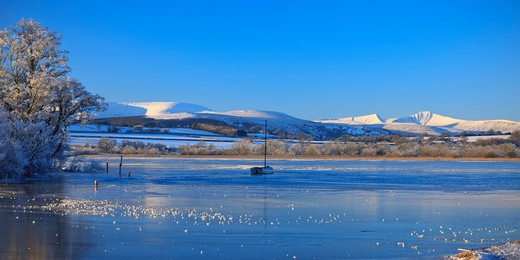 Stock Photo: 4282-5985 Wales, Powys, Brecon Beacons. A small sailing boat on the icy waters of Llangorse Lake in the Brecon Beacons National Park in winter. Pen y Fan & Corn Du mountains are in the background.