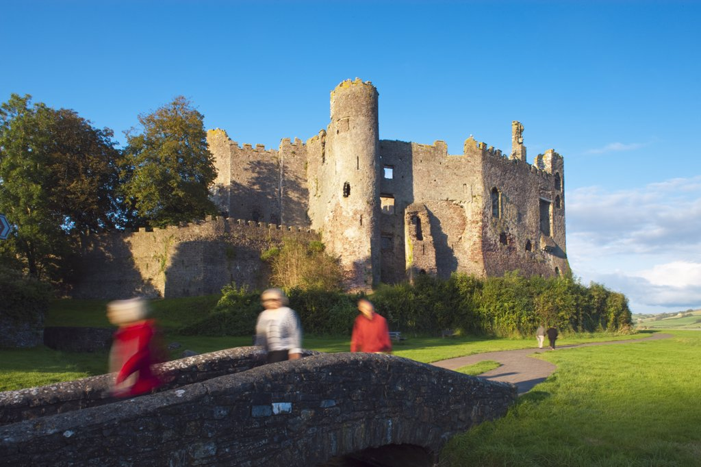 Stock Photo: 4282-6066 Wales, Carmarthenshire, Laugharne. Visitors crossing a footbridge by Laugharne Castle, a thirteenth century castle converted to a Tudor mansion in the sixteenth century.
