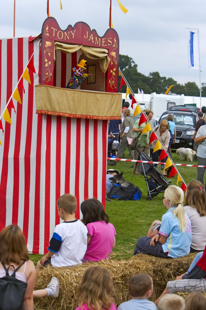 Stock Photo: 4282-6540 England, Gloucestershire, Frampton-on-Severn. Children sitting on bales of straw enjoying a Punch and Judy show at Frampton Country Fair.
