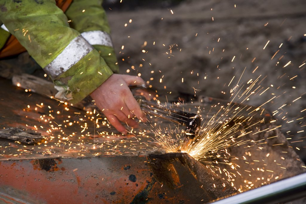 Stock Photo: 4282-6571 Engalnd, Wiltshire, near Avebury. A man welding during Silbury Hill renovation project.