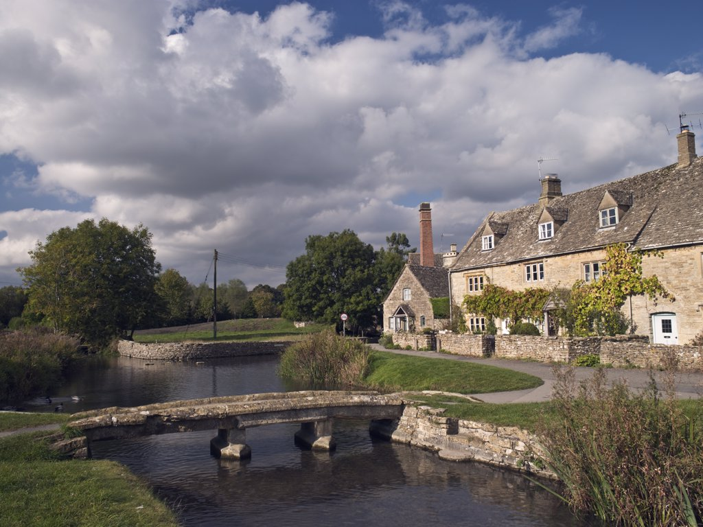 England, Gloucestershire, Lower Slaughter. A clapper bridge across the River Eye and the Old Mill in Lower Slaughter. : Stock Photo