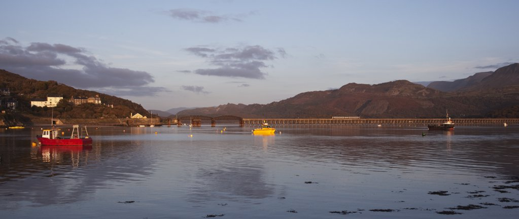 Wales, Gwynedd, Barmouth. Barmouth harbour and railway bridge - a train is crossing the bridge. : Stock Photo