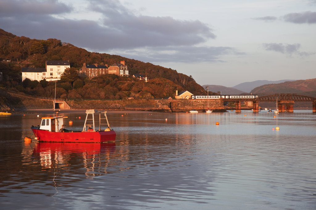 Stock Photo: 4282-6758 Wales, Gwynedd, Barmouth. Barmouth harbour and railway bridge - a train is crossing the bridge.