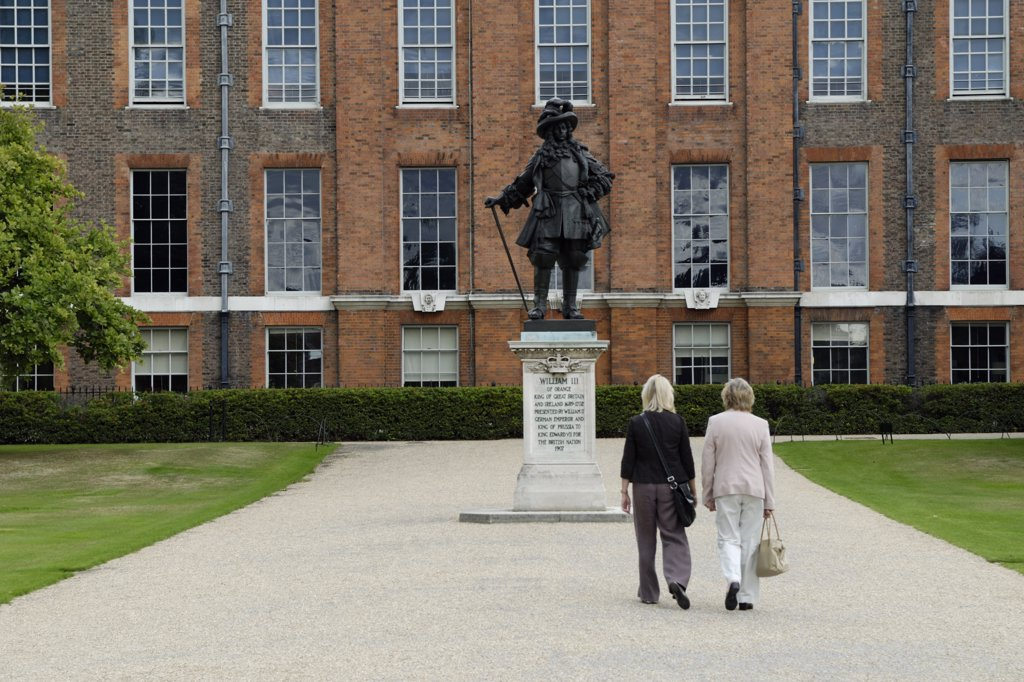 Stock Photo: 4282-6977 England, London, Kensington. Two tourists walking towards the statue of William III in front of Kensington Palace.