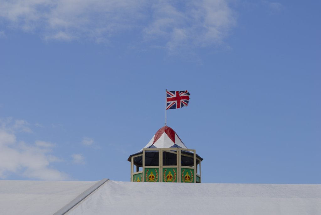 Stock Photo: 4282-7060 England, Kent, Detling. View across the top of a marquee to the top of a traditional helter skelter with the union jack flying on top at the kent Couty Show.