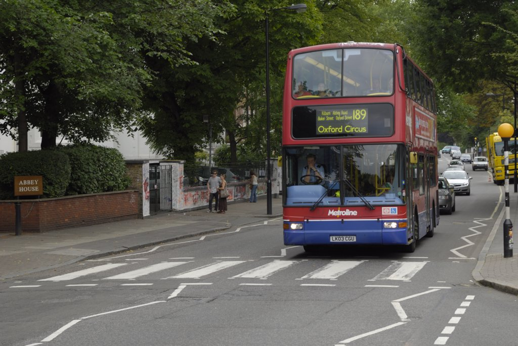 Stock Photo: 4282-7093 England, London, St John's Wood. A red London double decker bus stopped at the famous pedestrian crossing on Abbey Road which features on the cover of The Beatles album 'Abbey Road'.