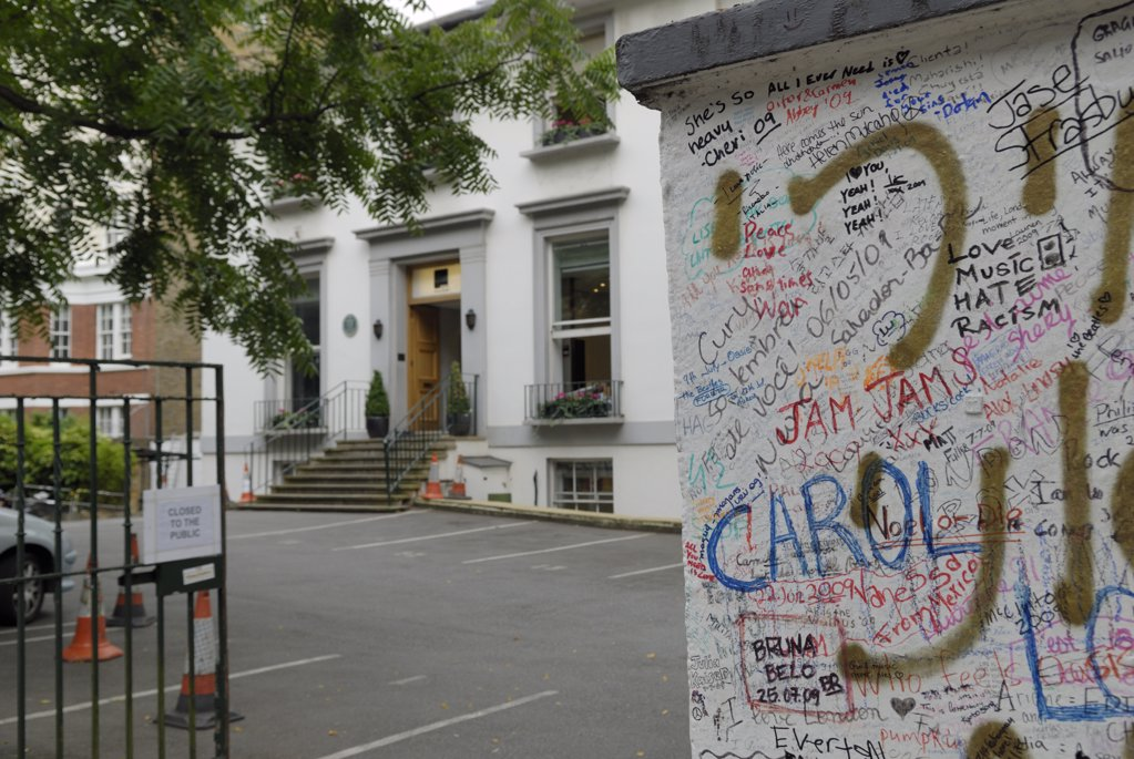 Stock Photo: 4282-7100 England, London, St John's Wood. Graffiti on the wall outside Abbey Road studios with the studios in the background.