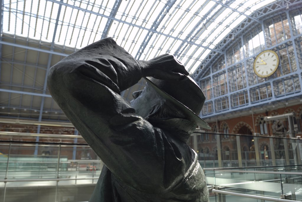 Stock Photo: 4282-7131 England, London, St Pancras Station. A statue of poet John Betjeman by Martin Jennings at St. Pancras International station, with the famous clock in the background.