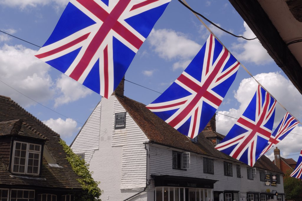 England, Kent, Brenchley. Bunting hanging underneath the overhang of a tudor house in celebration of the Tour de France passing through the village. : Stock Photo