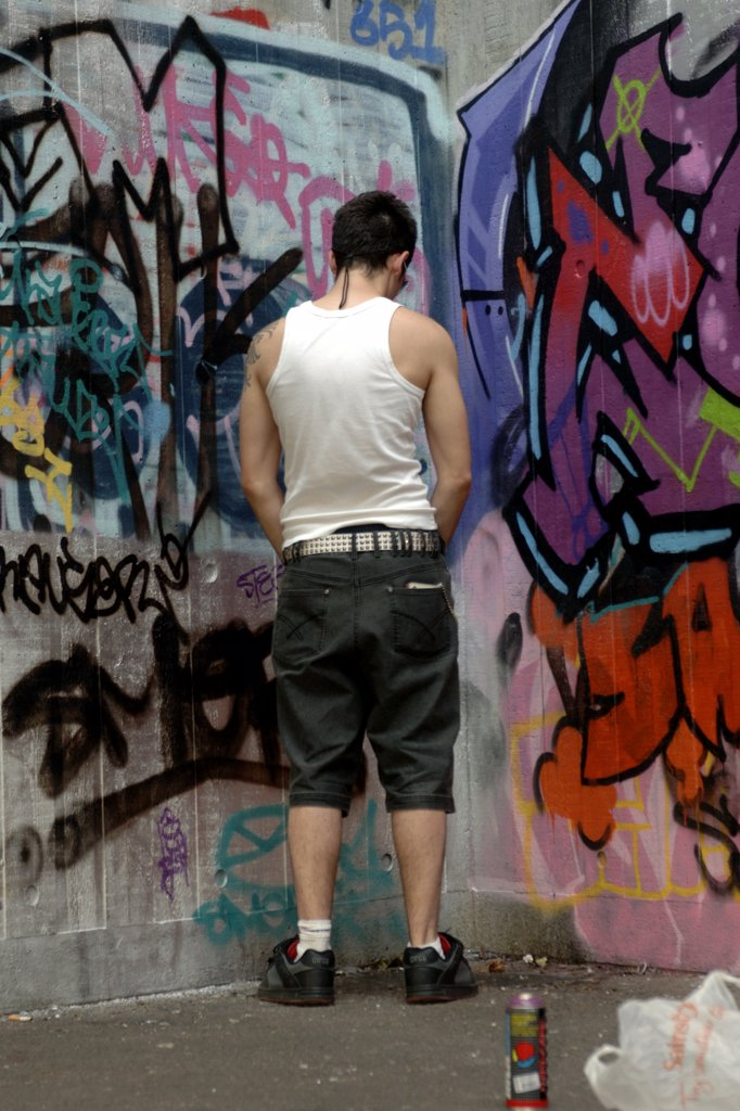 England, London, London. A youth relieving himself against a wall covered in graffiti on the south bank in London. The word 'graffiti' is the plural of 'graffito' and originates from the Italian word 'graffiato' which means scratched. : Stock Photo