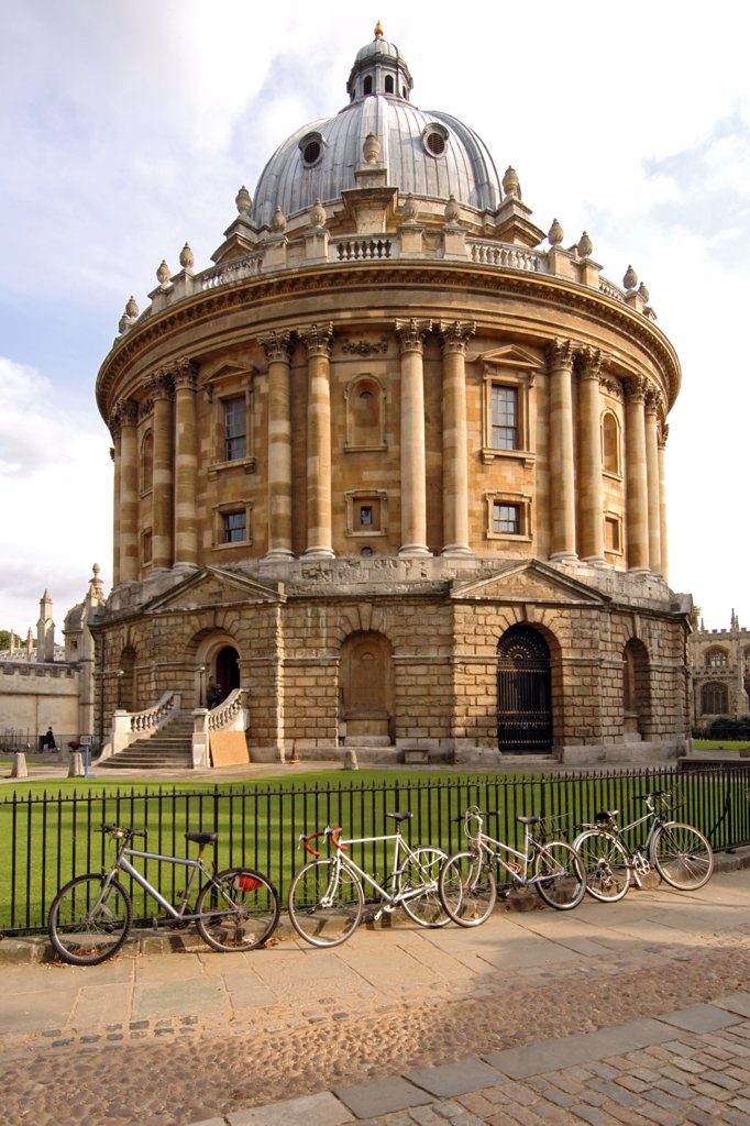 Stock Photo: 4282-7485 England, Oxfordshire, Oxford. Bicycles chained to the fence encircling the Radcliffe Camera building. Originally a science library, it has become a reading room of the Bodleian Library.