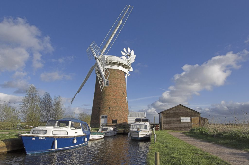 Stock Photo: 4282-7970 England, Norfolk, Horsey. Cabin boats moored by Horsey Windpump on the Norfolk Broads.